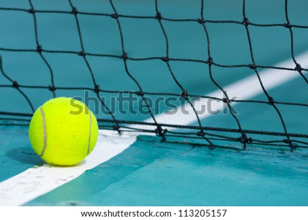 Tennis ball on the field. A mesh blocking out during the course. - stock photo