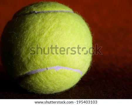 Tennis ball on the orange surface, closeup shot, useful for various, tennis,recreation and sport themes - stock photo