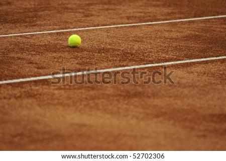 Tennis ball on the orange tenniscourt - stock photo