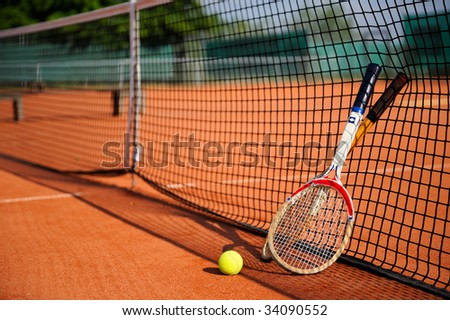 tennis ball, racket and net on the sand court - stock photo