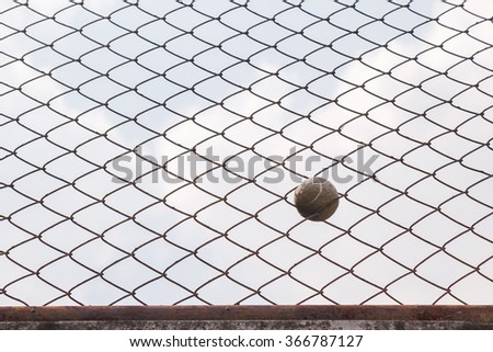 Tennis Ball Stuck In Fence The Net - stock photo