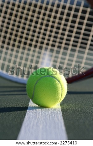 Tennis ball with a racquet in the background - stock photo