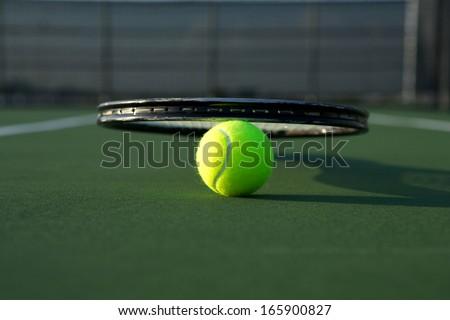 Tennis Ball with Racket Balanced on It - stock photo
