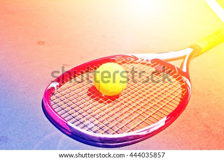 Tennis ball with racket on court with color filters - stock photo