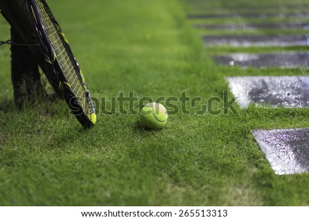 Tennis ball with racket on wet grass after raining, next to walkway - stock photo