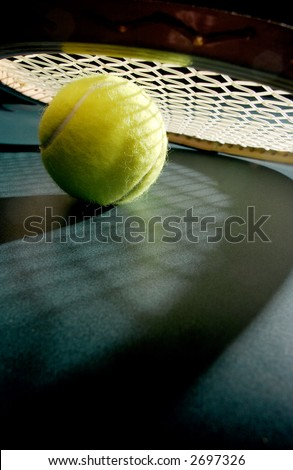 Tennis ball with racket & shadows - stock photo