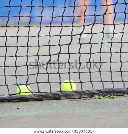 Tennis balls lies near the tennis net - stock photo