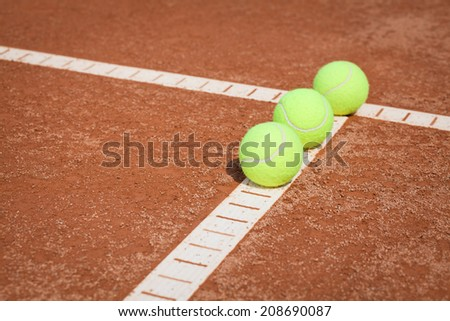 tennis balls on clay court - stock photo