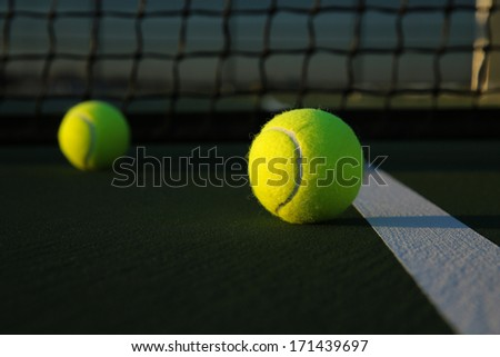 Tennis Balls on the Court Close up with the Net Beyond - stock photo
