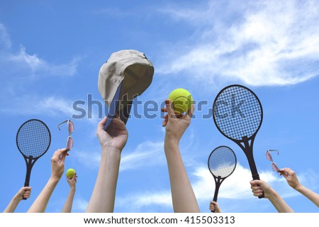 Tennis balls, sunglasses, racket, cap in hand. Blue sky background. Concept: friendship, relaxation, sports, summer. Good relax with friends.Sport is a useful and fun. - stock photo