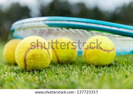 Tennis balls with a racket at the lawn court - stock photo