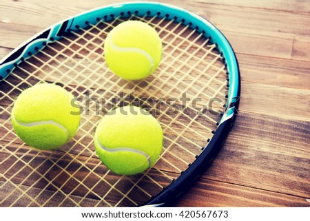 Tennis game. Tennis balls and racket on wooden background. Vintage retro picture. - stock photo