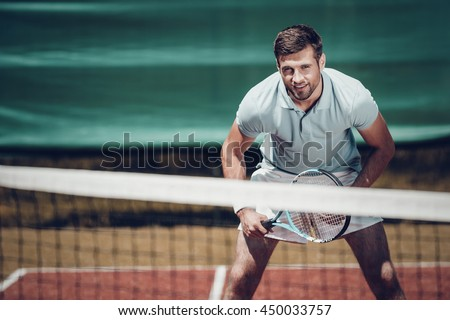 Tennis player. Handsome young man in polo shirt holding tennis racket and smiling while standing on tennis court - stock photo