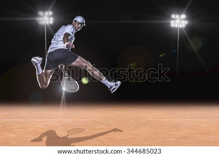 Tennis player jumping for the ball behind on tennis court - stock photo