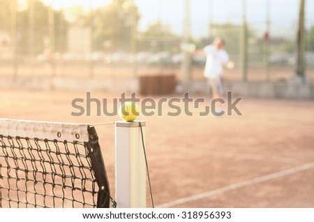 Tennis player on a clay court with a ball on a net post in focus suggesting a tennis match with a warm sunny bright look with soft filter effects applied - stock photo