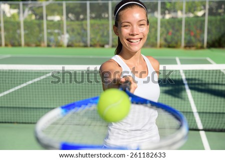 Tennis player portrait. Woman showing tennis ball and racket smiling happy. Female athlete inviting you to play tennis. Healthy active sport and fitness lifestyle concept outdoor. - stock photo