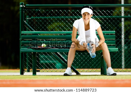 Tennis player rests with bottle of water on the bench at the tennis court - stock photo
