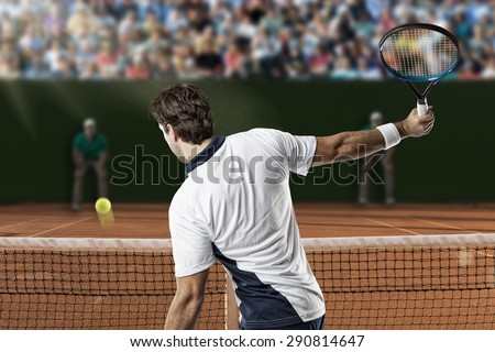Tennis player returning a ball on a clay tennis court. - stock photo