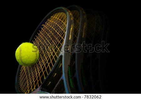 Tennis racket and ball on black background - stock photo