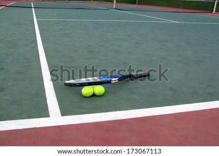 Tennis racket lying on a tennis balls near the court line - stock photo