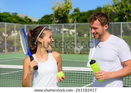 Tennis sport - couple relaxing after playing game of tennis outside in summer. Happy smiling friends on outdoor tennis court living healthy active fitness lifestyle. Woman and man athletes. - stock photo