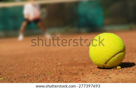 Tennis tennis ball on the ground and the player - stock photo