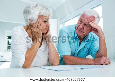 Tensed senior man and woman talking to each other at home - stock photo