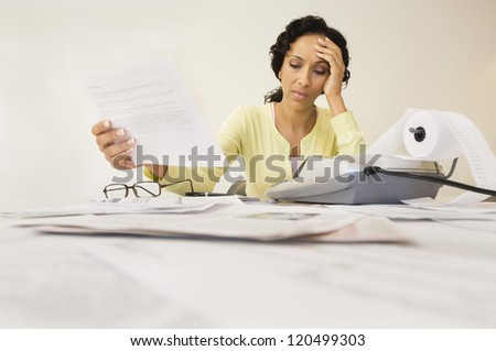 Tensed woman with expense receipt sitting at home - stock photo