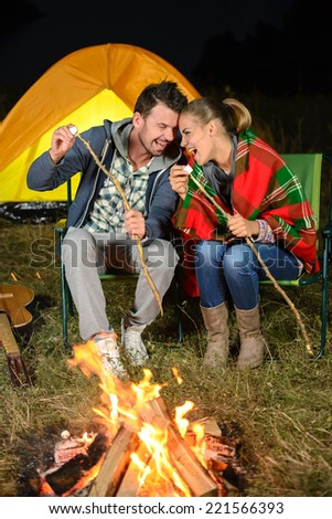 Tent camping couple romantic sitting by bonfire night countryside - stock photo