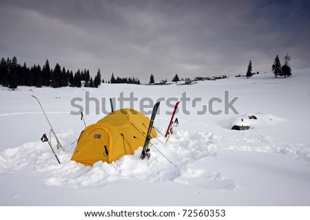 tent fitted with skis in snow in winter - stock photo