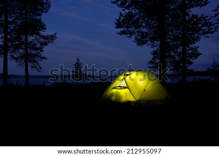 tent glowing in the darkness in the forest with lake, Russia, Karelia, 2014 - stock photo