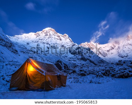 Tent in the mountains on a winter night with bright moon, Annapurna Sanctuary Nepal - stock photo