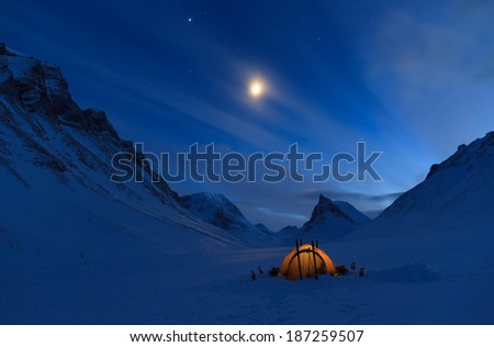 Tent in the mountains on a winter night with bright moon in Lapland. - stock photo