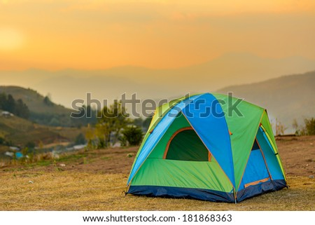 tent in the sunset overlooking mountains and a valley - stock photo