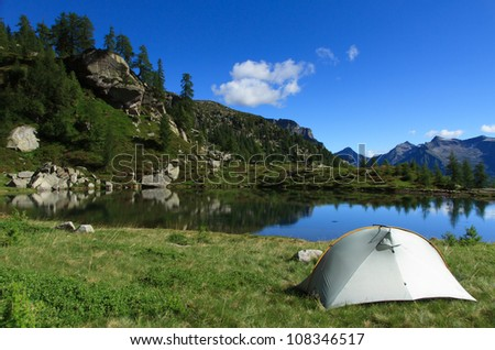 Tent on a campsite at a lake in the mountains. - stock photo