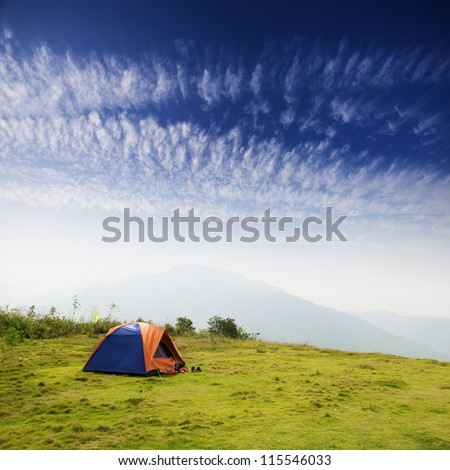 tent on a grass under white clouds - stock photo