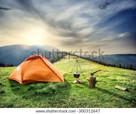 Tent on the hill beneath the mountains under dramatic sky - stock photo
