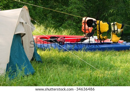 Tent set up for camping by a river - stock photo