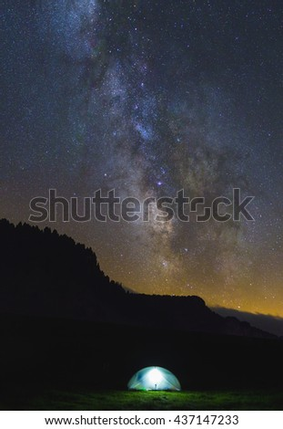 Tent under the night sky and milky way during a hiking trip in the mountains. - stock photo