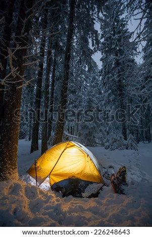 Tent with inside light in winter forest after sunset - stock photo