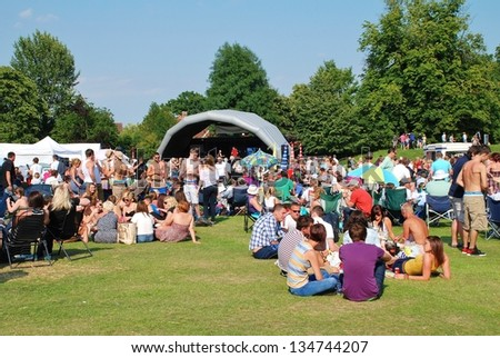 TENTERDEN, ENGLAND - JULY 3: The audience sitting on the grass at the Tentertainment music festival on July 3, 2011 at Tenterden, Kent. The annual free festival was first held in 2008. - stock photo