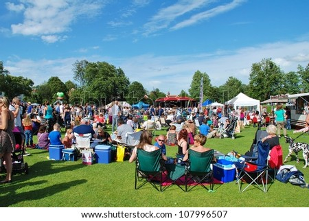 TENTERDEN, ENGLAND - JUNE 30: The audience sitting on the grass at the Tentertainment music festival on June 30, 2012 at Tenterden, Kent. The annual free event was first held in 2008. - stock photo
