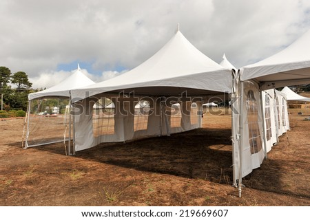 Tents in a field with some brown grass outside - stock photo