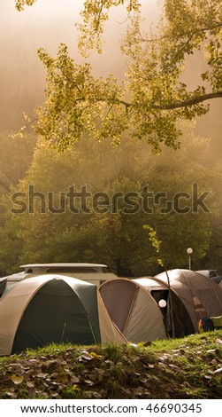 tents in camp site with green trees and early morning mist - stock photo
