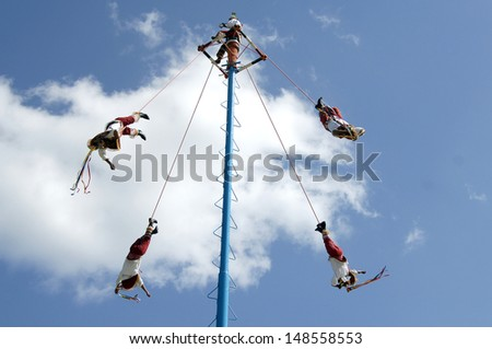 TEOTIHUACAN, MEXICO: The ancient ritual for a great harvest. Mexicans in national clothes perform traditional ritual descent down from a high pole. - stock photo