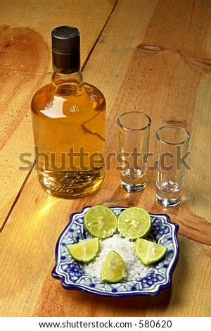 tequila bottle and stuff on a wood table - stock photo