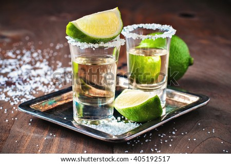 Tequila gold, Mexican, alcohol in shot glasses, lime and salt, toned image, selective focus - stock photo