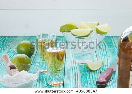 tequila in glasses and    lime fruits on turquoise colored wooden table - stock photo