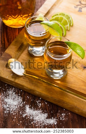 Tequila in shot glasses with lime and salt - stock photo