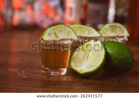 tequila , lime and salt on wooden  table selective focus - stock photo